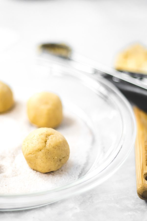 Raw snickerdoodle dough in the form of a ball on sugar coating.