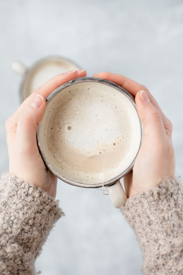 Two hands holding up a mug containing London fog latte for two.