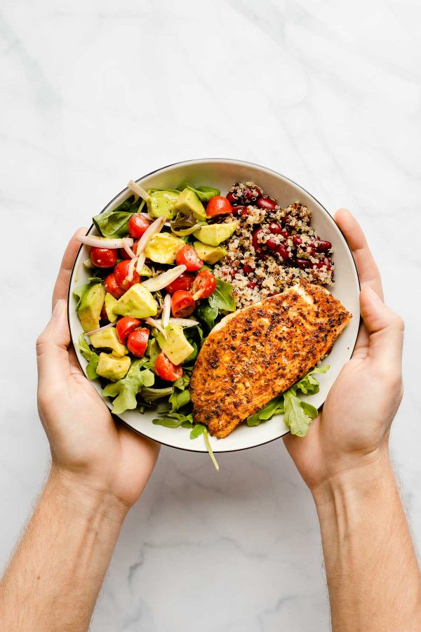 Two hands holding a plate of a plate containing blackened white fish with quinoa, red kidney beans and a mixed salad with tomatoes and avocado on top.