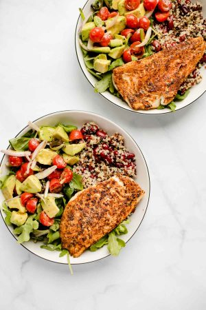 Top view of two plates containing blackened white fish with quinoa, red kidney beans and a mixed salad with tomatoes and avocado on top.