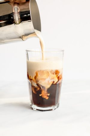 Milk being poured over iced coffee to make a boozy iced coffee.