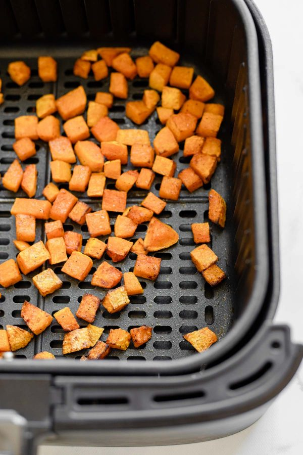 Close up of roasted butternut squash made and in an air fryer basket.