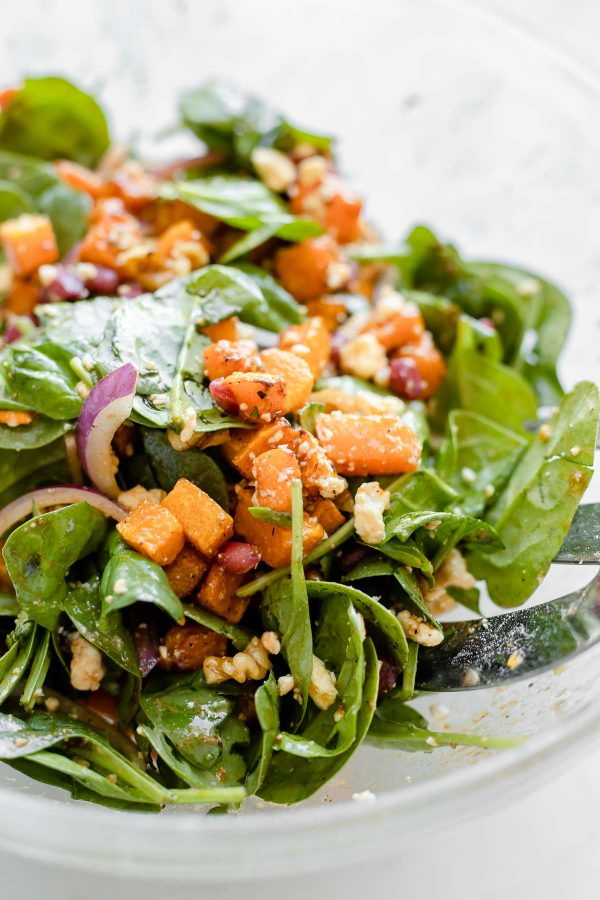 Close up of tossed butternut squash and pomegranate salad.