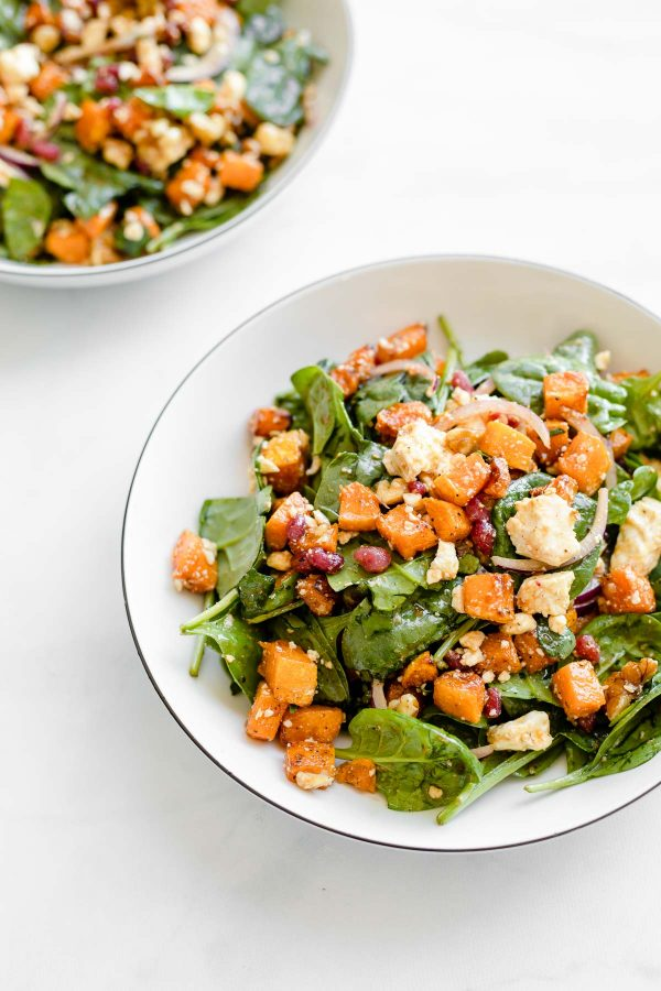Angled view of two bowls of butternut squash and pomegranate salad.