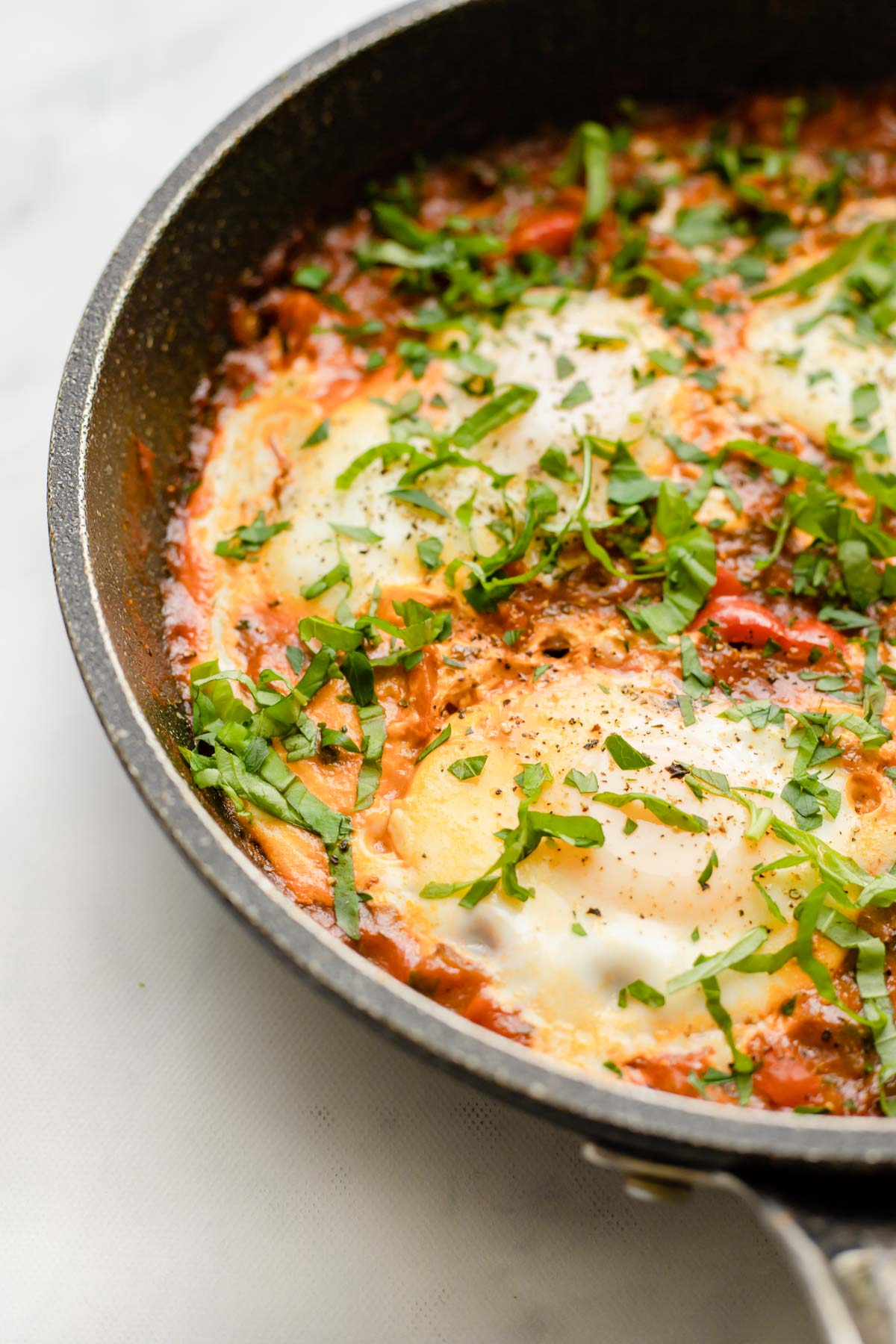 Close up of eggs cooked in a tomato sauce making eggs in purgatory.