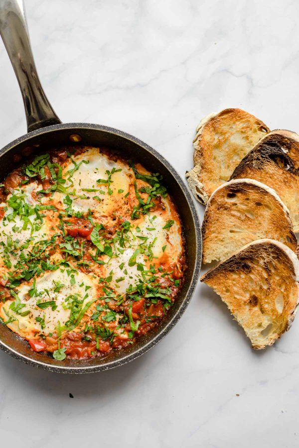 A pan with eggs in purgatory and sliced toasted bread beside.
