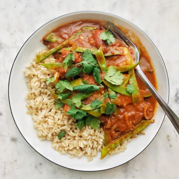Arial view of a plate of moroccan stewed haddock with a side of brown rice topped with cilantro leaves.