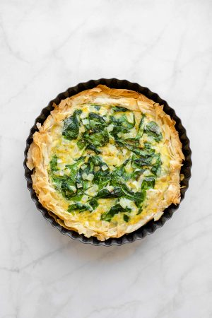 Top view of a freshly baked spanakopita quiche.