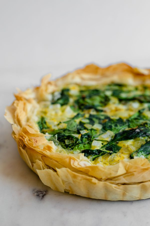 Side view of the flaky phyllo crust of a spanakopita quiche.