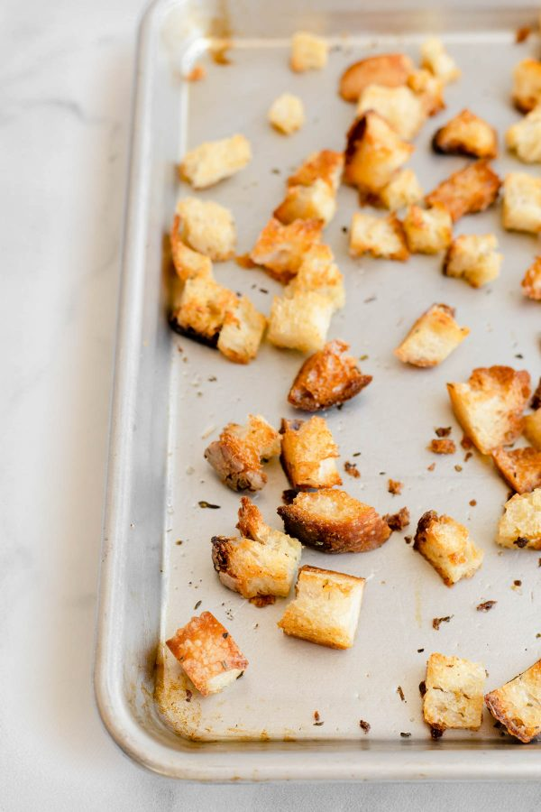 Close up of baked croutons on a baking sheet.