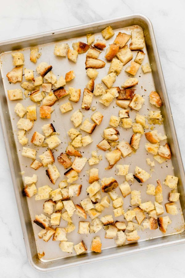 Torn pieces of bread tossing in oil and seasonings on a baking sheet.