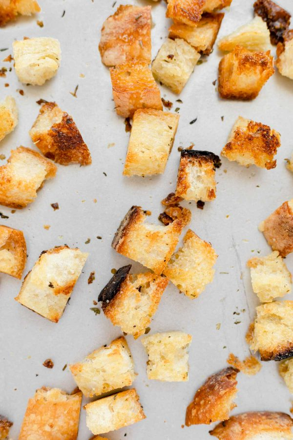 Close up showing the golden colour of cooked croutons on a baking sheet.