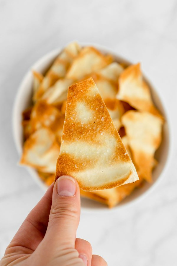 A pita chip being help up by a hand over a bowl of chips.