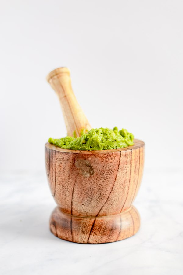A wood mortar and pestle with smashed guacamole inside.