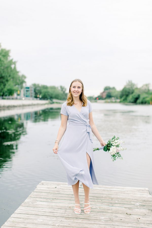 Photo of a woman in a blue dress on a wood dock.