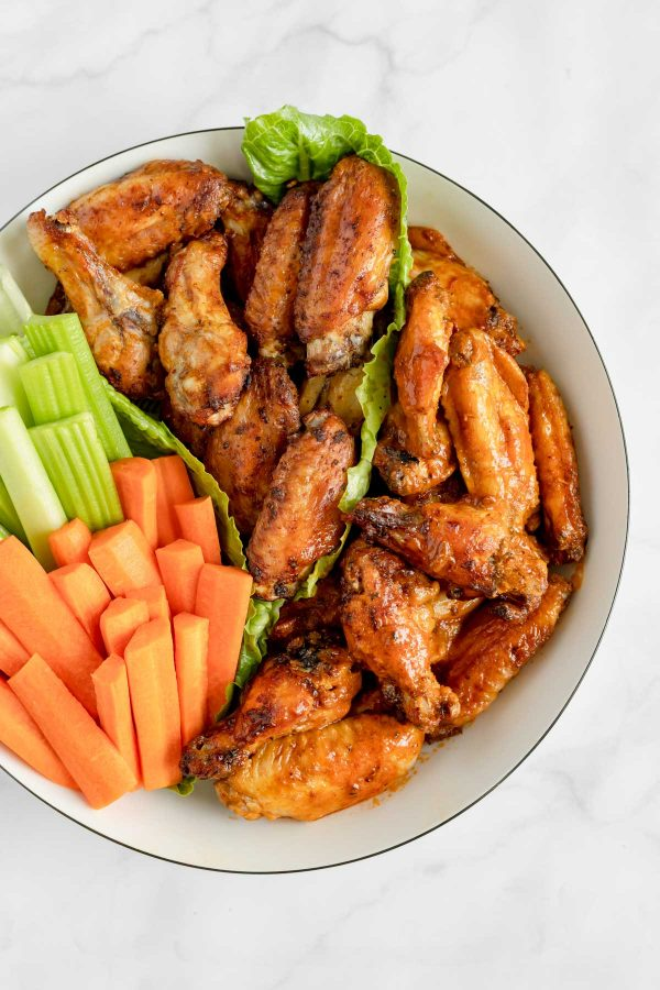 Platter of chicken wings two ways: dry and crispy and coated with buffalo sauce.