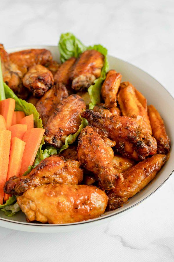 Close op of crispy air fryer chicken wings on a platter.