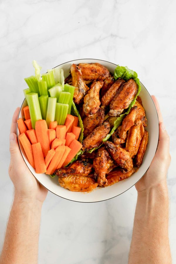 Hands holding a platter of chicken wings two ways: dry and crispy and coated with buffalo sauce.