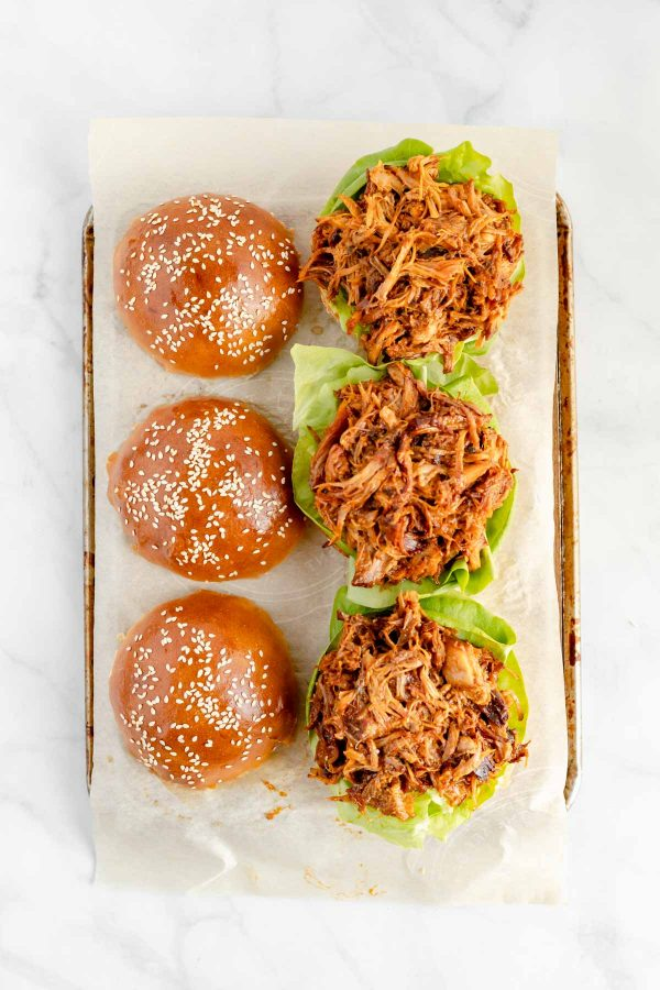 Top view of three pulled pork sandwiches without tops (tops are resting beside them).