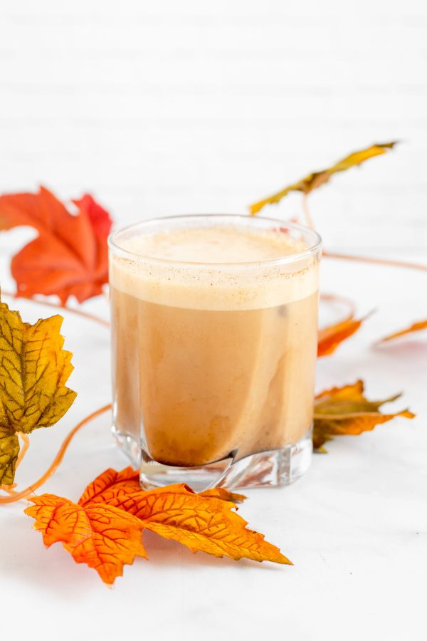 Glass tumbler with pumpkin cream cold brew showing the foamy topping surrounded with orange/yellow/green fall leaves.