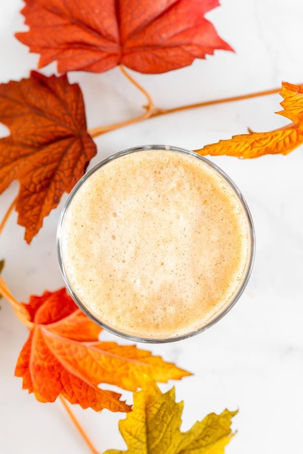 Top view of a glass tumbler showing pumpkin cream cold foam with leaves in the foreground.