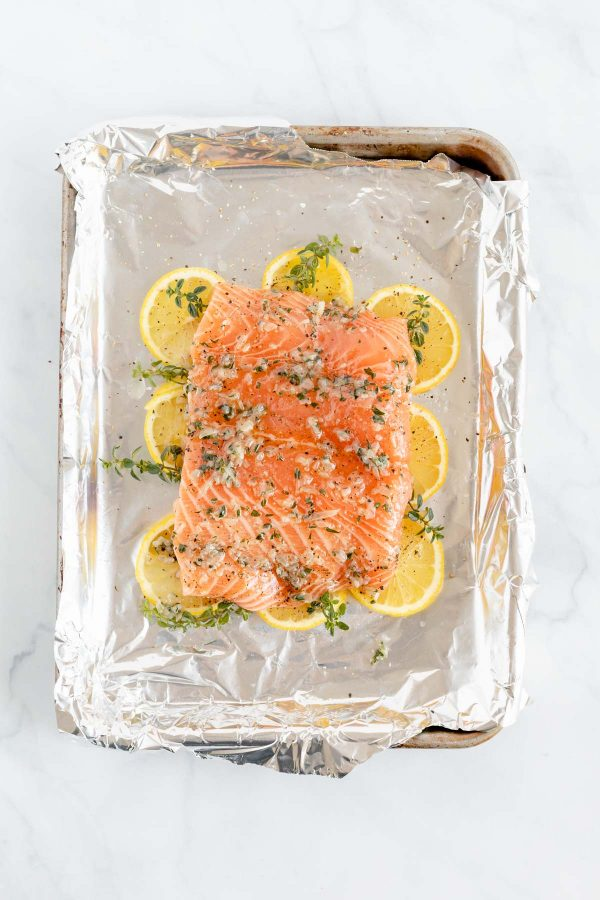 Top view of a piece salmon resting on a bed of lemons and thyme springs.
