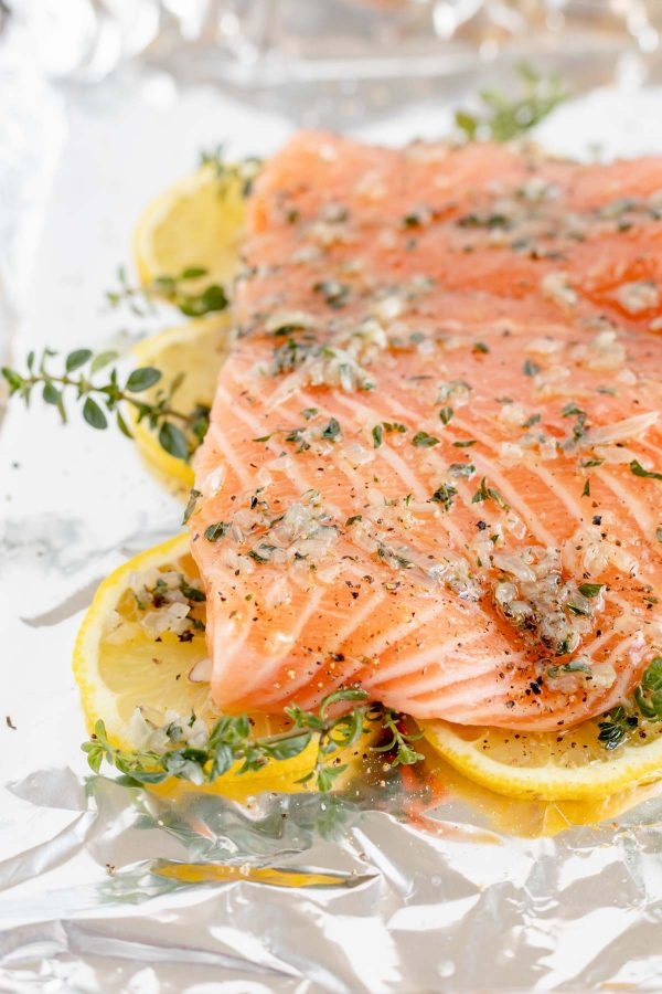 Close up of a salmon covered in butter, thyme and shallots on a lemon bed.