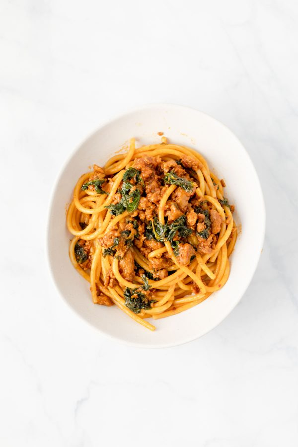 Top view of a bowl containing sausage and caramelized shallot ragu with greens tossed with bucatini.