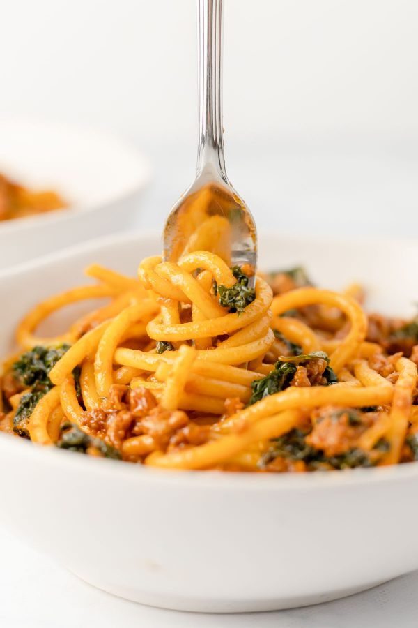 Close up of a fork swirling bucatini coated in sausage and caramelized shallot ragu with greens sauce.