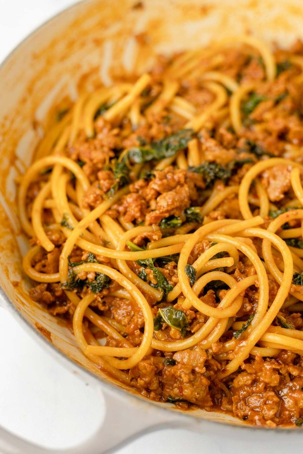 Close up of a sauce pan containing sausage and caramelized shallot ragu with greens tossed with bucatini.