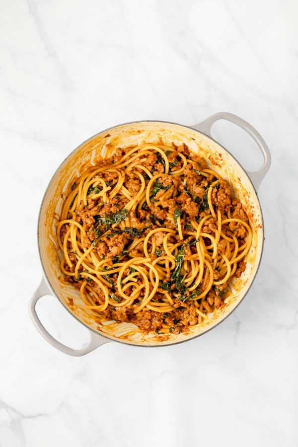 Top view of a sauce pan containing sausage and caramelized shallot ragu with greens tossed with bucatini.
