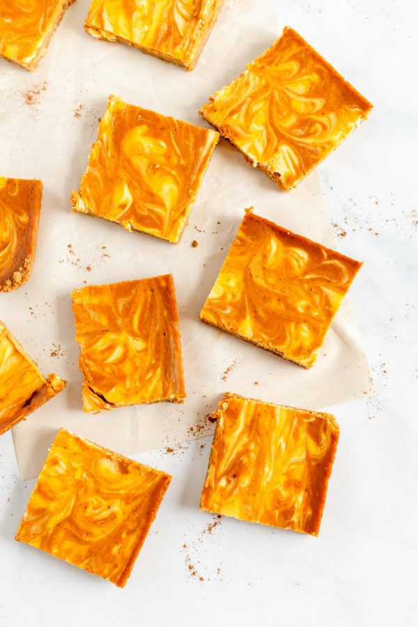 Cut pumpkin cheesecake swirl bars on top of parchment paper.