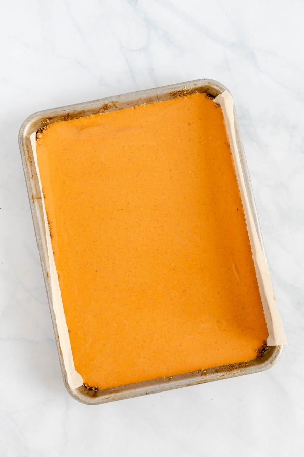 Rimmed quarter baking sheet containing pumpkin bars before the addition of a cheesecake swirl and baking.